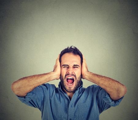 ruido: Retrato de hombre joven gritando con la boca abierta, la cabeza con las manos sosteniendo, vestido con camisa azul casual, aislado sobre fondo gris de la pared. rostro humano emoción expresión
