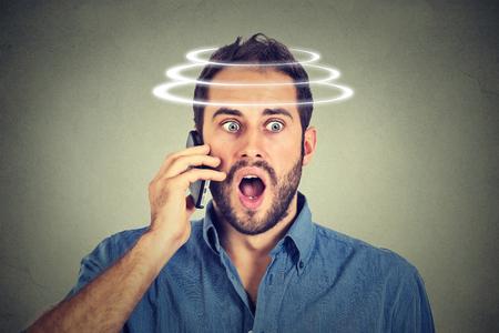 Head is spinning vertigo dizziness. Portrait shocked man talking on mobile phone. Bad news. Modern gadgets and health issues