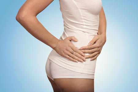 ovaire: Jeune femme de toucher son c�t� droit dans la douleur. L'inflammation du rein et de la th�rapie. M�decine et le concept de soins de sant�. Fond bleu