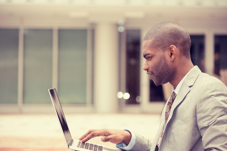 african business: Side profile handsome young businessman working using laptop outdoors, browsing internet. Instagram filter effect Stock Photo