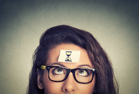 Time management concept young woman with sand clock sign sticker on her forehead