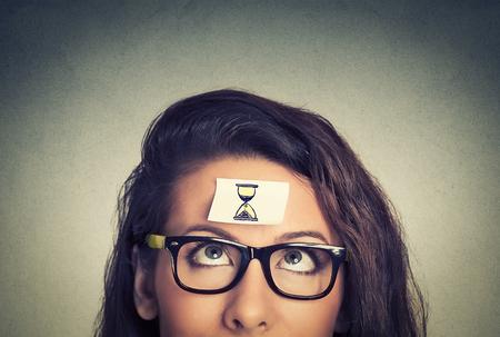 Time management concept jonge vrouw met zand klok sticker teken op haar voorhoofd Stockfoto
