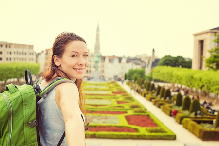 belgique: Happy young woman in Brussels downtown extending you an arm inviting to visit Mont des Arts garden