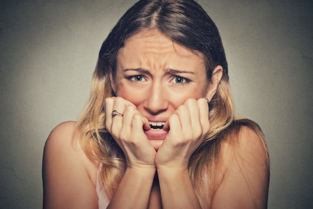 Closeup portrait headshot nervous stressed young woman girl student biting fingernails looking anxiously craving something isolated grey wall background. Human emotion face expression feeling