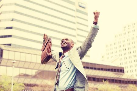 libertad: Joven apuesto hombre de negocios celebra éxito la libertad brazos levantados riendo mirando al cielo. Emociones humanas positivas enfrentan sentimientos de expresión. Carrera logro vida concepto de la libertad financiera