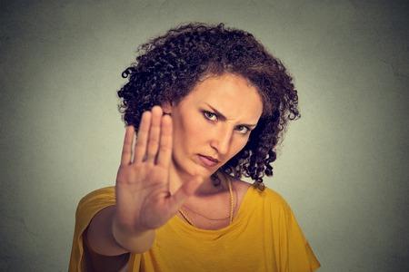 enojo: Retrato de joven mujer enojar molesto primer con la mala actitud que da hablar con gesto de la mano con la palma hacia afuera aislado fondo de la pared gris. Cara emoci�n negativa lengua sensaci�n expresi�n cuerpo humano Foto de archivo