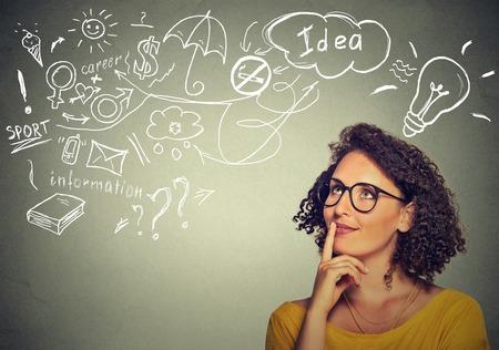 idée: Portrait jeune femme heureuse pensée rêve a beaucoup d'idées regardant mur gris fond isolé. Expression du visage de la vie sentiment émotion perception humaine positive. La prise de décision concept de processus.
