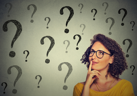 asking question: Thinking young business woman in glasses looking up at many question marks isolated on gray wall background