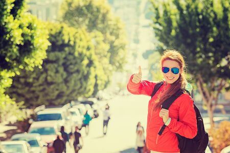 woman bag: Beautiful smiling young woman with sunglasses and backpack in San Francisco city on a sunny warm autumn day. Positive emotions face expression. Instagram style yellow filter image