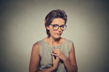 Lack of confidence. Shy young woman in glasses feels awkward isolated on grey wall background. Human emotion body language life perception Stock Photo