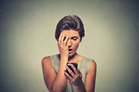 lenguaje corporal: Malestar subrayó mirando el teléfono móvil que sostiene la mujer disgustada sorprendido con el mensaje que recibió aislado fondo gris. Emoción expresión humana sintiendo reacción lenguaje corporal percepción vida Foto de archivo