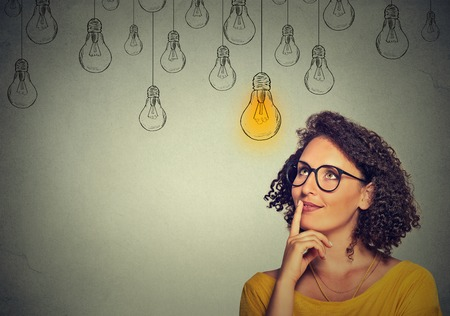 female face: Portrait thinking woman in glasses looking up with light idea bulb above head isolated on gray wall background