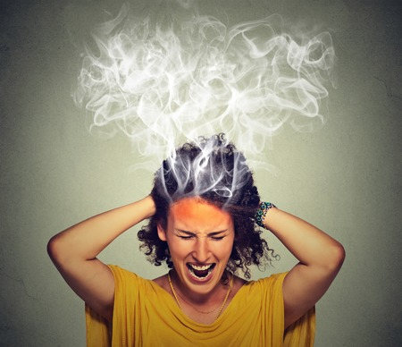 angry teacher: Portrait young stressed woman screaming frustrated thinking too hard steam coming out up of head isolated on grey wall background. Human face expression emotion perception Stock Photo