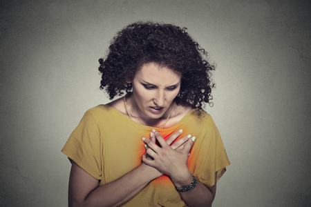 nude young woman: sick middle aged woman with heart attack, pain, health problem holding touching her chest colored in red with hands isolated on gray wall background. Human face expression