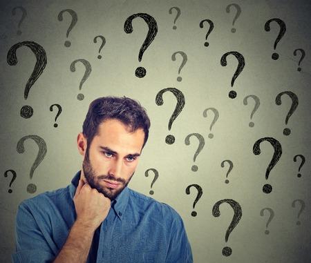 Bezorgd trieste man heeft veel vragen op zoek naar beneden op een grijze muur achtergrond. Menselijk gezicht meningsuiting emotie gevoel perceptie