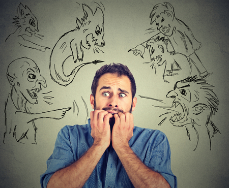 judged: Bad evil men pointing at stressed man. Desperate scared young businessman isolated on grey office wall background. Negative human emotions face expression feelings life perception Stock Photo