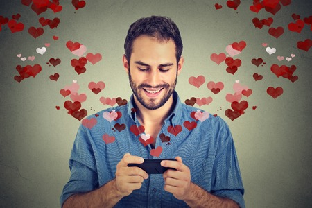 dating: Portrait happy man sending love sms text message on mobile phone with red hearts flying away from screen isolated on grey wall background. Human emotions Stock Photo