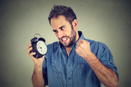 oversleep: Portrait upset angry young man screaming at alarm clock isolated on gray wall background. Employee running late. Time management concept