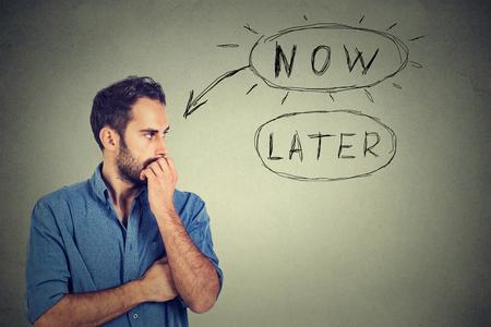 Nyní nebo později. Muž myšlení kousal nehty ustaraným výrazem úzkosti, které tvoří jeho mysl izolovaných na šedém pozadí zdi. Výraz lidskou tváří