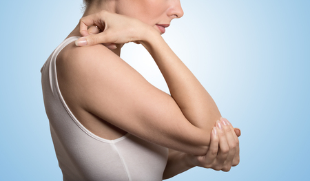 bones: Cropped image woman with joint inflammation. Females elbow. Arm pain and injury concept. Closeup side profile woman with painful elbow isolated on blue background