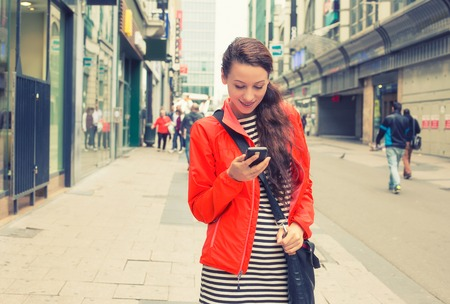 mobile business: Happy girl texting on the smart phone walking down the street wearing a red jacket in autumn