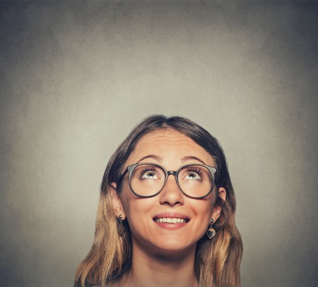 Closeup of woman in glasses looking up isolated on gray wall background