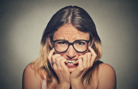 embarrassed: Closeup portrait nervous stressed young woman girl in glasses student biting fingernails looking anxiously craving something isolated on grey wall background. Human emotion face expression feeling