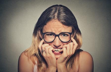 ansiedad: Retrato del primer nervioso destacó joven mujer en gafas de estudiantes uñas morder mirando ansiosamente antojo de algo aislado en el fondo de la pared gris. La emoción humana sensación de expresión de la cara
