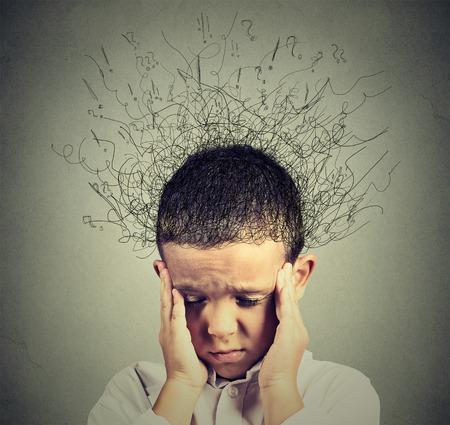kinderen: Closeup droevige jongen met ongerust benadrukte gezichtsuitdrukking zoek naar beneden met hersenen smelten in lijnen vraagtekens. Obsessieve compulsieve, ADHD, angststoornissen begrip