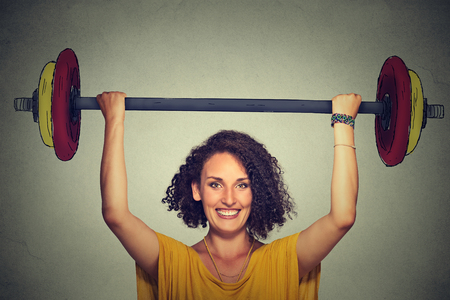 determinism: Happy strong young man lifting barbell above head with two hands Stock Photo