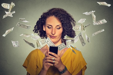 corporate waste: Technology online banking money transfer e-commerce concept. Annoyed young woman using smartphone with dollar bills flying away from screen isolated gray wall office background. Human face expression