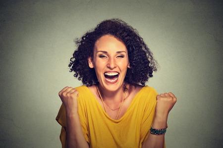 Gelukkige vrouw exults pompen vuisten extatische feest succes op grijze achtergrond