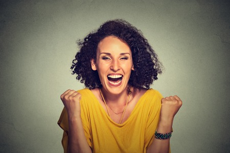 happy woman exults pumping fists ecstatic celebrates success on gray background Stock Photo