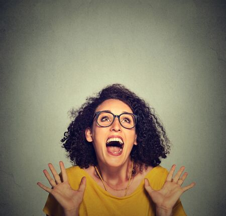 exaggerate: super excited funky girl looking up isolated on grey wall background