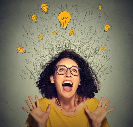 Close-up super enthousiast gelukkig schreeuwende vrouw met veel lichte idee lampen boven het hoofd viert succes te kijken op grijze muur achtergrond
