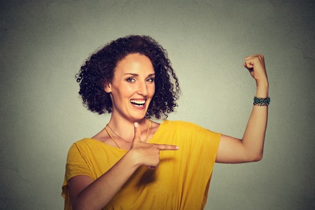 woman muscle: Closeup portrait fit middle aged healthy model woman flexing muscles confident showing her strength isolated on gray background. Positive emotion facial expression feeling attitude perception