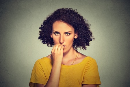 uptight: Worries. Closeup portrait nervous looking woman biting her fingernails craving something anxious isolated on gray wall background. Negative human emotion facial expression body language perception