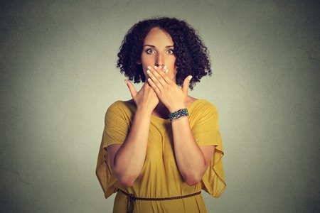 boca cerrada: Closeup portrait young woman covering closed mouth with hands. Speak no evil concept isolated on grey wall background. Human emotion face expression sign symbol. Social media news coverup
