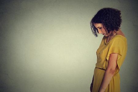 avergonzado: Perfil lateral triste joven solitaria mirando hacia abajo aislado en el fondo de la pared gris. las emociones humanas, la expresión de la cara