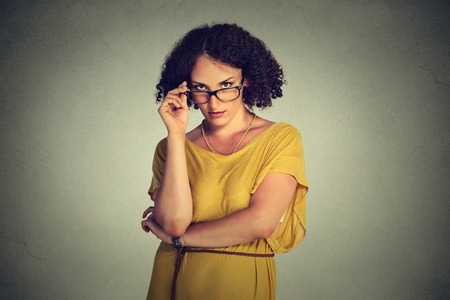 trouble: Angry bitchy serious woman with glasses in yellow dress skeptically looking at you isolated on gray wall background. Human face expression, body language, attitude, perception, vision