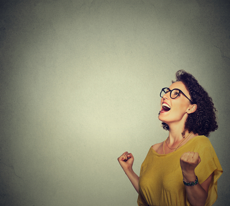 portrait happy woman in yellow dress exults pumping fists ecstatic celebrates success Stock Photo
