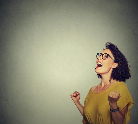celebra: retrato mujer feliz en vestido amarillo exults puños de bombeo de éxtasis celebra el éxito