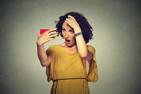 クローズ アップ不幸不満若い女性驚いた彼女は後退生え際の髪を失っています。灰色の背景。人間の顔の表現感情。美容ヘアスタイル コンセプト