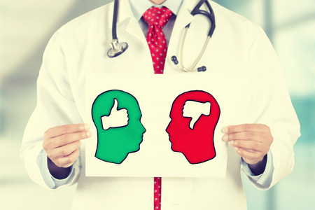 Closeup doctor hands holding white card with green red thumbs up thumbs down symbols inside signs shaped as human head isolated on hospital clinic office background. Retro instagram style filter image 写真素材