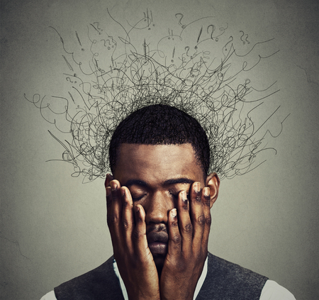 fear: Depressed worried young man with worried desperate stressed expression hands covering face and brain melting into lines question marks. Depression, anxiety disorders, life failure. Gray background