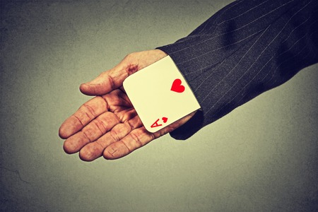 deceive: Closeup cropped image senior man hand pulling out a hidden ace from the sleeve isolated on gray wall background
