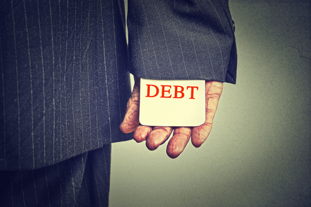 financial burden: Debt concept. Closeup business man hiding debt card in a suit sleeve