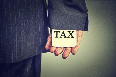 Korruption illegale kriminelle Aktivitäten Steuerhinterziehung Wirtschaft Ponzi-Schema-Konzept. Nahaufnahmemann Hand versteckt Steuerkarte in einer Hülse einer auf grauen Wand Hintergrund Anzug Standard-Bild - 48484795
