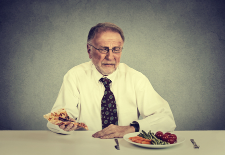 cravings: Say no to fast junk food. Senior man eating fresh vegetable salad avoiding fatty pizza. Healthy diet nutrition choices concept