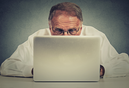 difficult lives: Closeup portrait elderly man sitting at table working on laptop computer isolated on gray office wall background Stock Photo